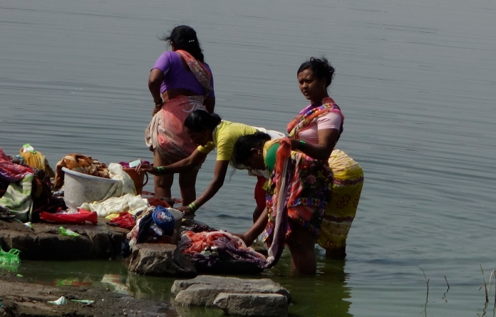 Women washing clothes in lake